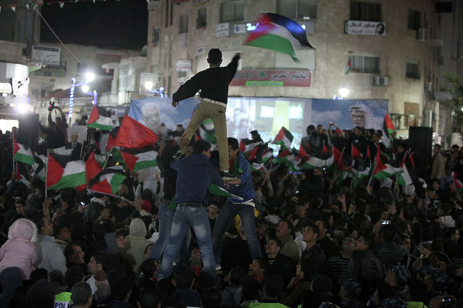 Palestinians celebrate in the West Bank city of Ramallah on November 29, 2012 after the General Assembly voted to recognise Palestine as a non-member state. The UN General Assembly on Thursday voted overwhelmingly to recognize Palestine as a non-member state, giving a major diplomatic triumph to president Mahmud Abbas despite fierce opposition from the United States and Israel. AFP PHOTO / ABBAS MOMANI Photo: ABBAS MOMANI, AFP/Getty Images / 2012 AFP