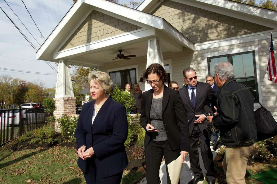 Mayor Annise Parker, left, walks down the sidewalk of a new