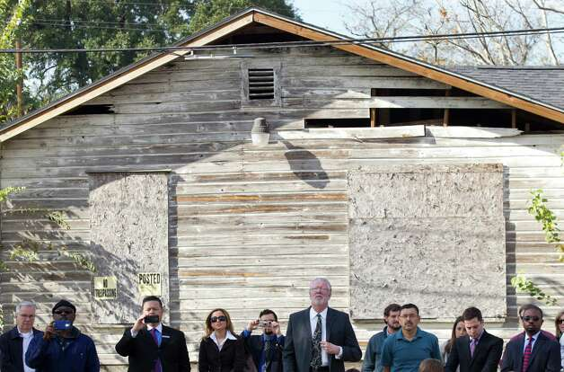 "People stand with their backs to an abandoned house as they watch a news conference to unveil of a pair of ""zero energy"" homes by HOUZE in Independence Heights Thursday, Nov. 29, 2012, in Houston. Photo: Brett Coomer, Houston Chronicle / © 2012 Houston Chronicle"
