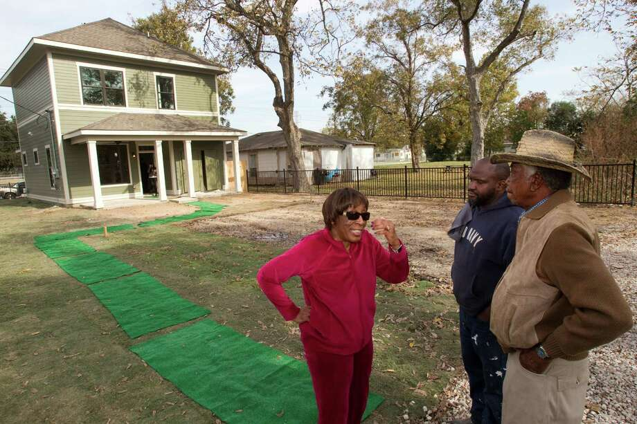 "Daisy Snow, left, Kelvin Williams and Cecil Snow, Sr., talk outside one of the two new ""zero energy"" homes by HOUZE built in Independence Heights Thursday, Nov. 29, 2012, in Houston. Photo: Brett Coomer, Houston Chronicle / © 2012 Houston Chronicle"