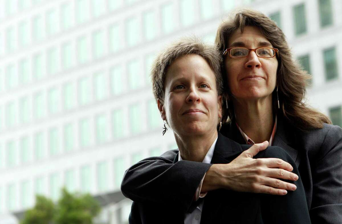 FILE - This Dec. 17, 2010 file photo shows Karen Golinski, right, hugging her wife Amy Cunninghis as they pose for a photograph outside of a federal court building in San Francisco. The fight over gay marriage is shifting from the ballot box to the Supreme Court.