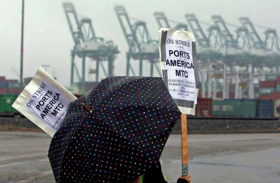 A clerical worker pickets in the rain at the Maersk cargo terminal, where container-handling cranes are in the up and idle position, background, at the Port of Los Angeles Thursday, Nov. 29, 2012.  Cargo ships were stacking up at the ports of Los Angeles and Long Beach as a strike by about about 70 clerical workers shut down most of the terminals that together are the nation's busiest port complex.  Dockworkers were refusing to cross the picket lines even though an arbitrator ruled the walkout invalid on Tuesday.  By Thursday morning, at least 18 ships docked and inside the adjacent harbors were not being serviced, port spokesmen said. (AP Photo/Nick Ut) Photo: Nick Ut