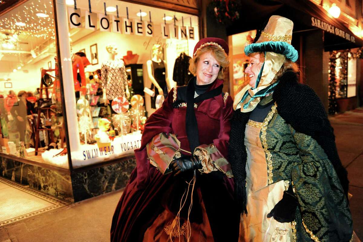 Cheryl Montanye, left, and Lisa O'Day, both on vacation from Hope Sound, Fla. show their Victorian style during the Victorian Streetwalk on Thursday, Nov. 29, 2012, on Broadway in Saratoga Springs, N.Y. (Cindy Schultz / Times Union)