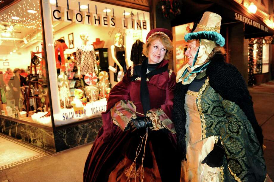 Cheryl Montanye, left, and Lisa O'Day, both on vacation from Hope Sound, Fla. show their Victorian style during the Victorian Streetwalk on Thursday, Nov. 29, 2012, on Broadway in Saratoga Springs, N.Y. (Cindy Schultz / Times Union) Photo: Cindy Schultz /  00020251A