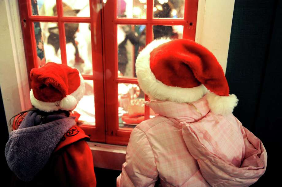 Trudie Herlihy, 5, left, and her sister, Meghan, 8, peek inside Santa's workshop during the Victorian Streetwalk on Thursday, Nov. 29, 2012, on Broadway in Saratoga Springs, N.Y. (Cindy Schultz / Times Union) Photo: Cindy Schultz /  00020251A