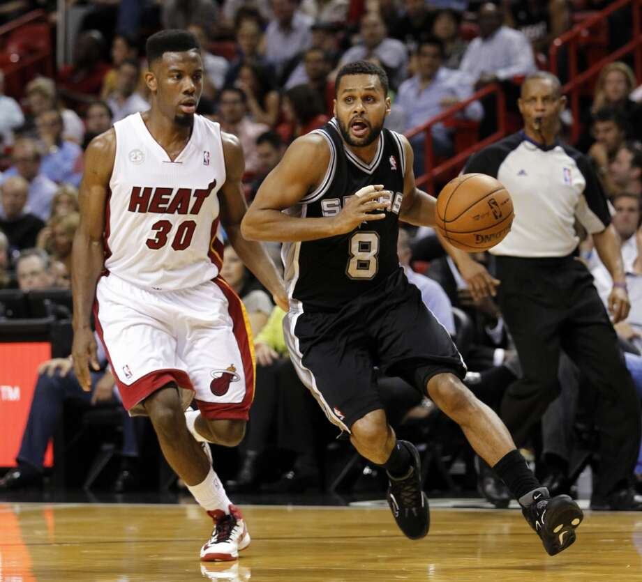 San Antonio Spurs' Patrick Mills (8) drives around Miami Heat's Norris Cole (30) in the first half of an NBA basketball game on Thursday, Nov. 29, 2012, in Miami.