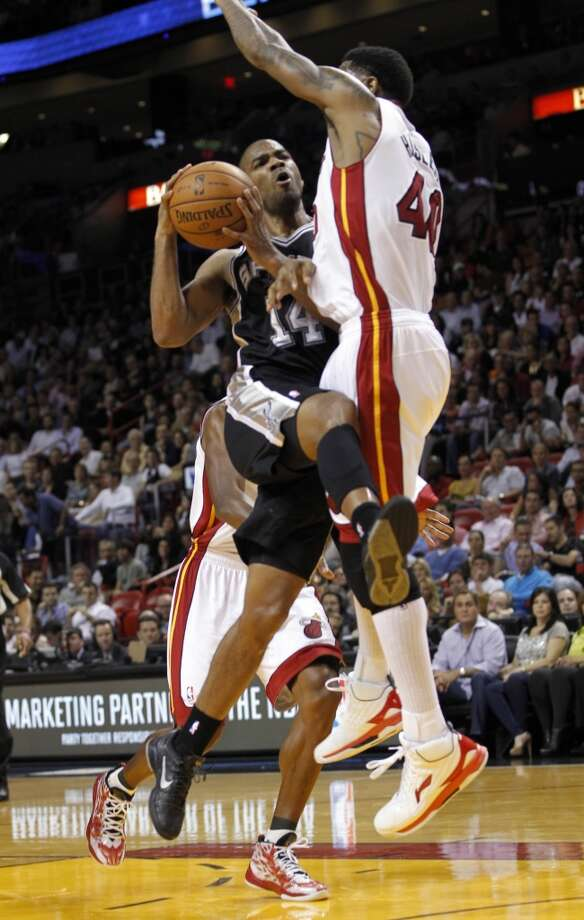 San Antonio Spurs' Gary Neal (14) is fouled by Miami Heat's Udonis Haslem (40) in the first half of an NBA basketball game on Thursday, Nov. 29, 2012, in Miami.
