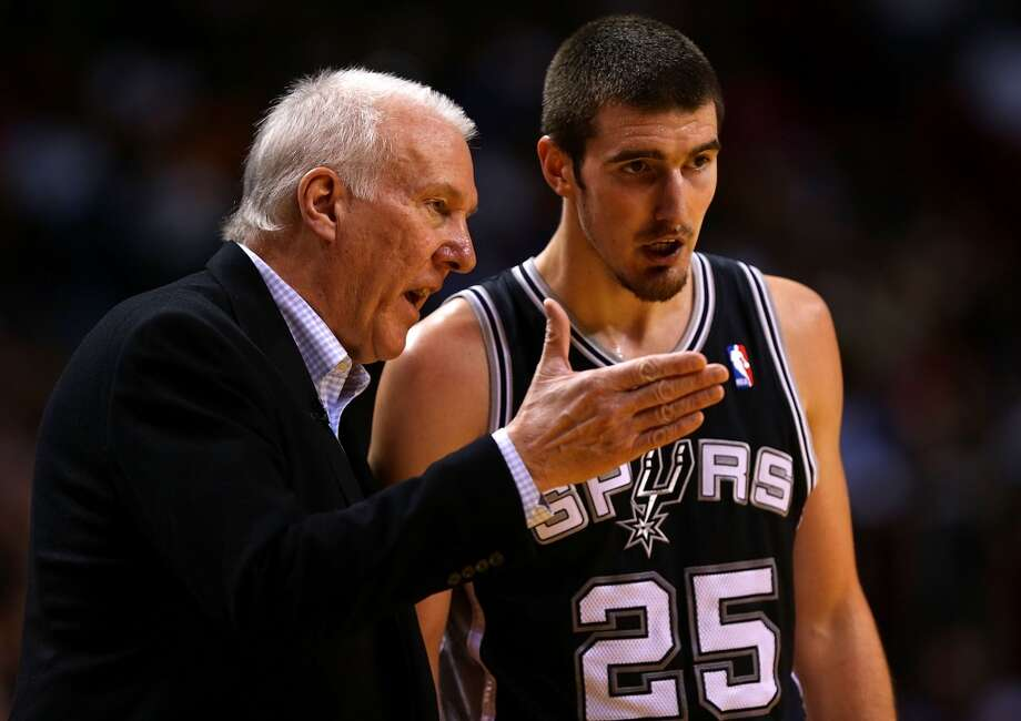 Nando de Colo #25 of the San Antonio Spurs talks with head coach Greg Popovich during a game against the Miami Heat at American Airlines Arena on November 29, 2012 in Miami, Florida.