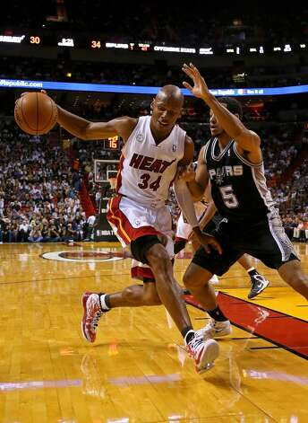 Ray Allen #34 of the Miami Heat drives on Cory Joseph #5 of the San Antonio Spurs during a game  at American Airlines Arena on November 29, 2012 in Miami, Florida.