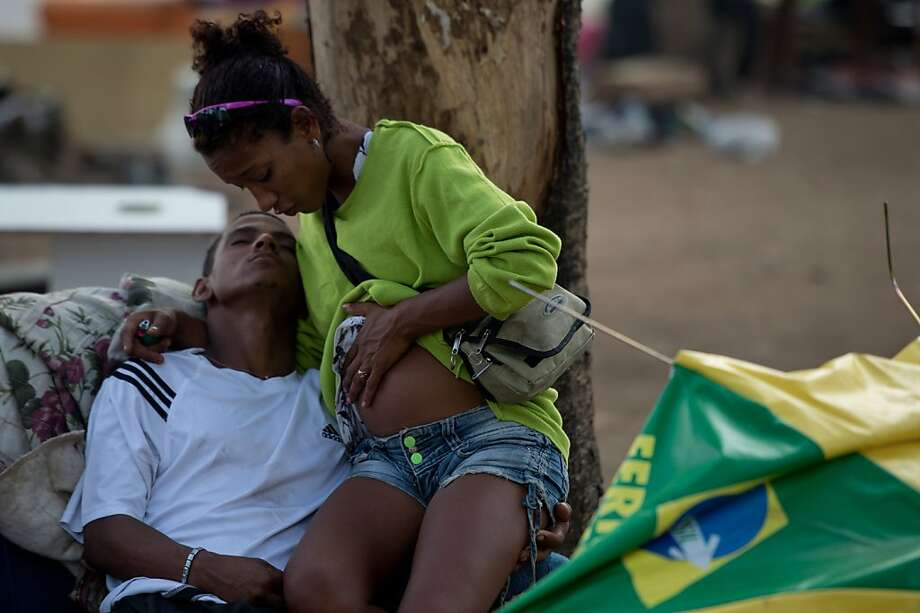 "TOPSHOTS  An alleged crack addict pregnant woman holds her boy friend at ""crackland"", near Parque Uniao slum during a police-sanitary operation in Rio de Janeiro on November 29, 2012, Brazil.  AFP PHOTO / CHRISTOPHE SIMONCHRISTOPHE SIMON/AFP/Getty Images Photo: Christophe Simon, AFP/Getty Images"
