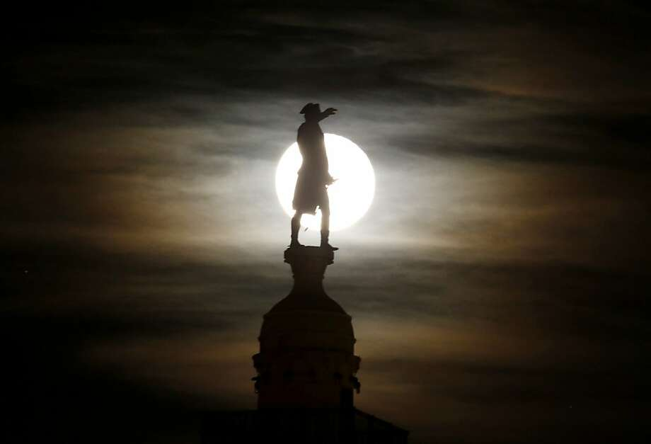 A bronze statue of General George Washington by William Rudolf O'Donovan stands on top of the Trenton Battle Monument while silhouetted by a the light of a full moon shinning on clouds, Thursday, Nov. 29, 2012, in Trenton, N.J. The monument commemorates the victory at the first Battle of Trenton, which occurred on Dec. 26, 1776, and is located where the artillery dominated the streets of Trenton, preventing the Hessian troops from organizing attacks. (AP Photo/Julio Cortez) Photo: Julio Cortez, Associated Press