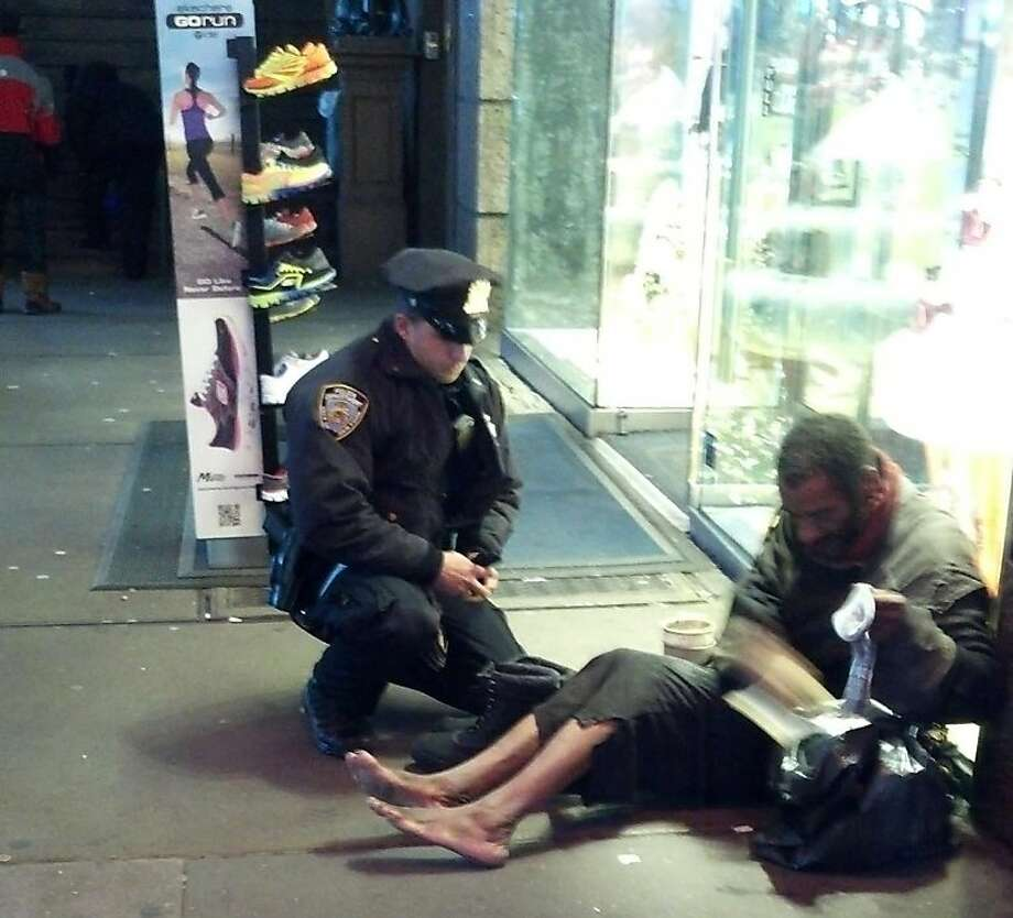 "This photo provided by Jennifer Foster shows New York City Police Officer Larry DePrimo presenting a barefoot homeless man in New York's Time Square with boots Nov. 14, 2012 . Foster was visiting New York with her boyfriend on Nov. 14, when she came across the shoeless man asking for change in Times Square. As she was about to approach him, she said the officer  came up to the man with a pair of all-weather boots and thermal socks on the frigid night. She took the picture on her cellphone. It was posted Tuesday night to the NYPD's official Facebook page and became an instant hit. More than 350,000 users ""liked"" it as of Thursday afternoon, and over 100,000 shared it. (AP Photo/Jennifer Foster) Photo: Jennifer Foster, Associated Press"