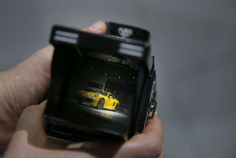 The new Porsche Cayman is seen through the viewfinder of a vintage TLR camera at the LA Auto Show in Los Angeles, Thursday, Nov. 29, 2012. (AP Photo/Jae C. Hong) Photo: Jae C. Hong, Associated Press