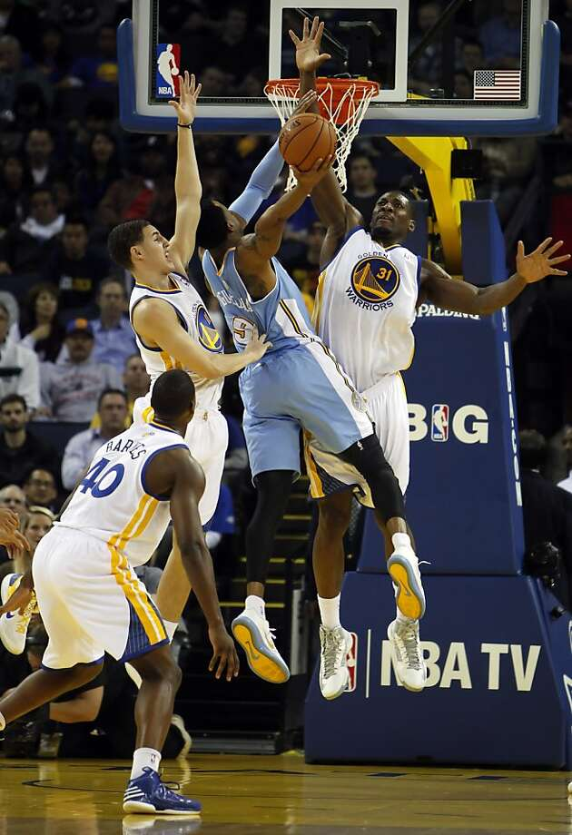 Klay Thompson, left, and Festus Ezeli, right, guard Denver's Andre Iguodala, center, in the first half. The Golden State Warriors played the Denver Nuggets at Oracle Arena in Oakland, Calif., on Thursday, November 29, 2012. Photo: Carlos Avila Gonzalez, The Chronicle