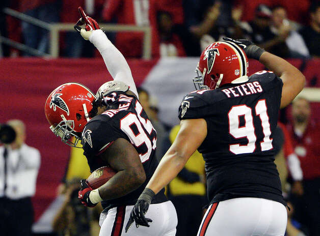 Atlanta Falcons defensive tackle Jonathan Babineaux (95) walks off the field with defensive tackle Corey Peters (91) after intercepting a pass from New Orleans Saints quarterback Drew Brees during the second half of an NFL football game, Thursday, Nov. 29, 2012, in Atlanta. The Falcons won 23-13. (AP Photo/Rich Addicks) Photo: Rich Addicks, FRE / FR170246 AP