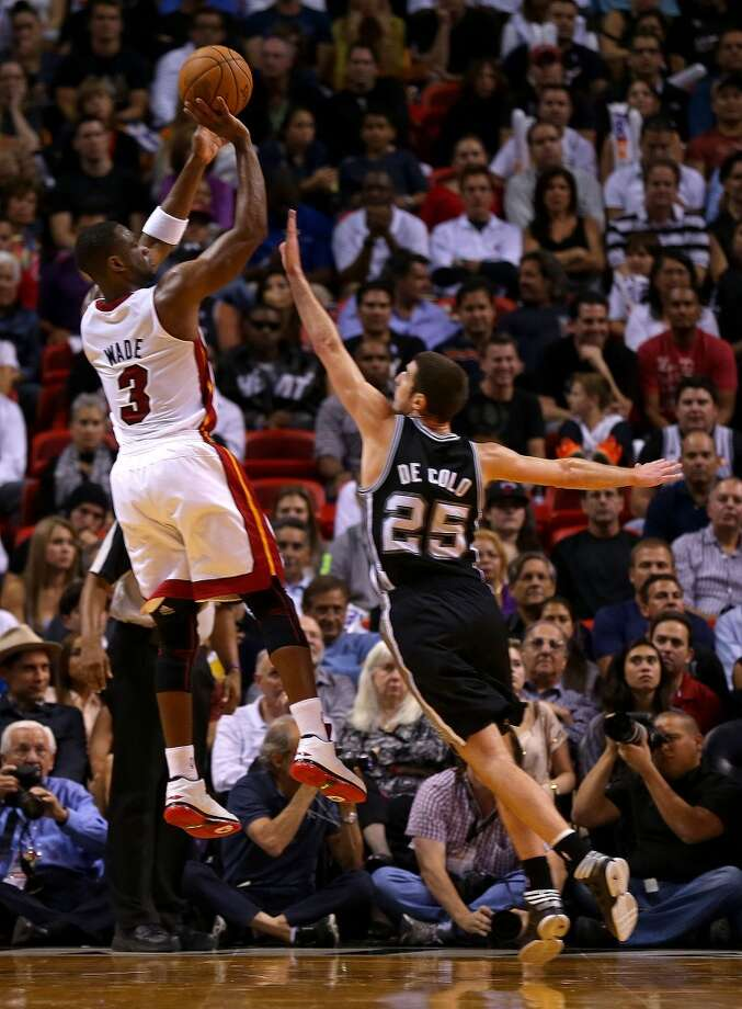 Dwyane Wade #3 of the Miami Heat shoots over Nando de Colo #25 of the San Antonio Spurs during a game  at American Airlines Arena on November 29, 2012 in Miami, Florida.