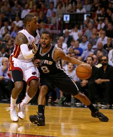 Patrick Mills #8 of the San Antonio Spurs drives on Mario Chalmers #15 of the Miami Heat during a game  at American Airlines Arena on November 29, 2012 in Miami, Florida.