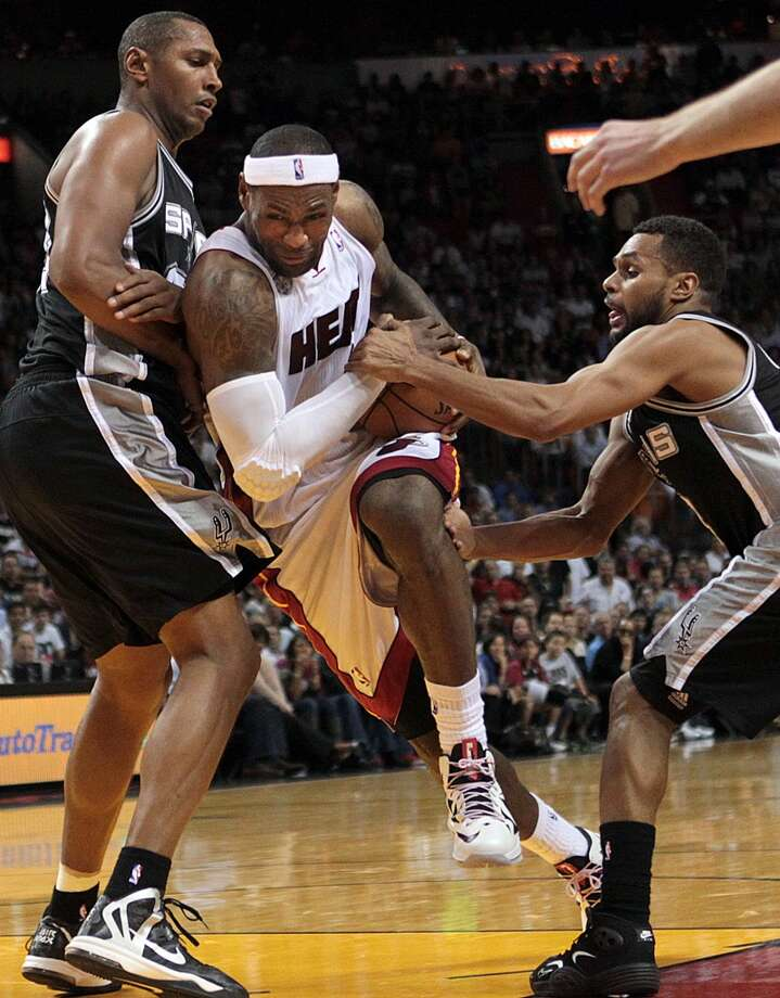 Miami Heat's LeBron James drives to the basket between San Antonio Spurs' Boris Diaw, left, and Patty Mills during the fourth quarter of an NBA basketball game in Miami on Thursday, Nov. 29, 2012. (AP Photo/El Nuevo Herald, Pedro Portal) MAGS OUT