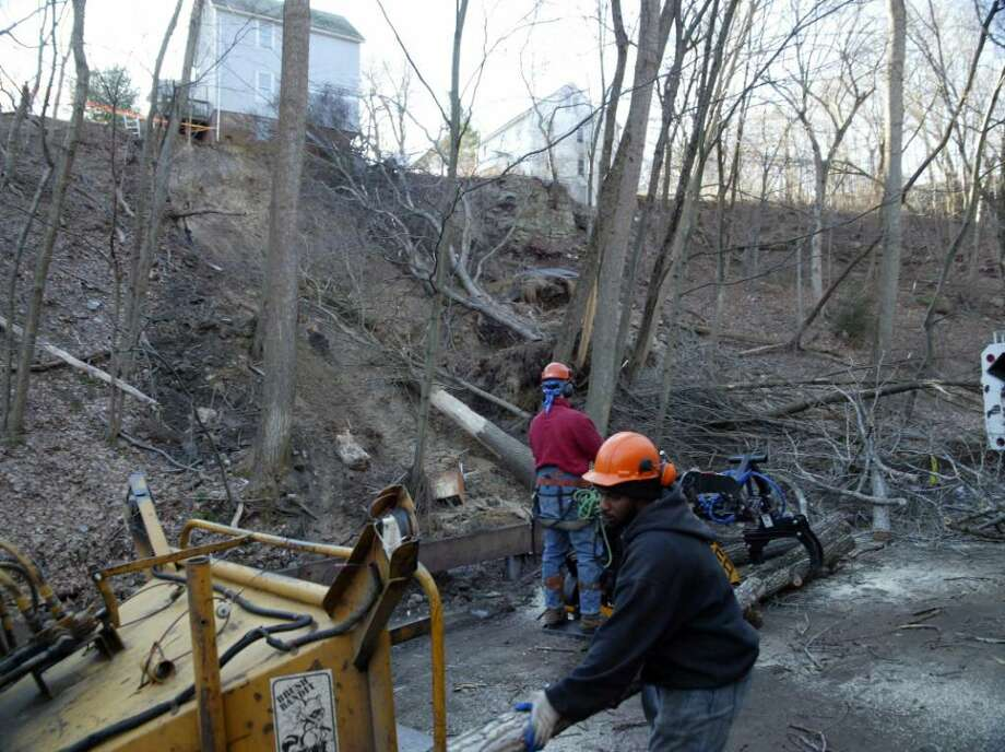 Workers, from ACER Tree Service in Trumbull, begin to clear the 150' cliff and Riverview condo parking lot of downed trees and other debris that came down with Tuesday's mudslide at 161 North Oak Avenue in Shelton. Thursday, Dec. 17, 2009. Photo: Phil Noel / Connecticut Post