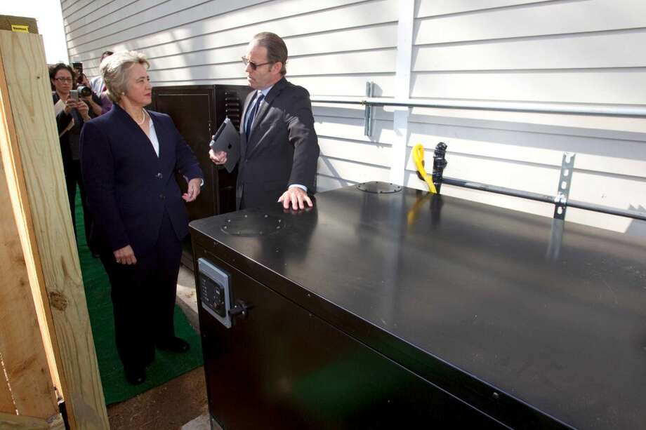 Mayor Annise Parker, left, listens as David Goswick, left, CEO of HOUZE, explains the power controls of a new zero energy home built  in Independence Heights Thursday, Nov. 29, 2012, in Houston. The initial rollout of HOUZE homes, using energy-wise next generation building systems, materials and technologies, was developed through a partnership with the City of Houston. The homes are designed to be so energy efficient that they can put energy back into the grid. ( Brett Coomer / Houston Chronicle ) (Houston Chronicle)