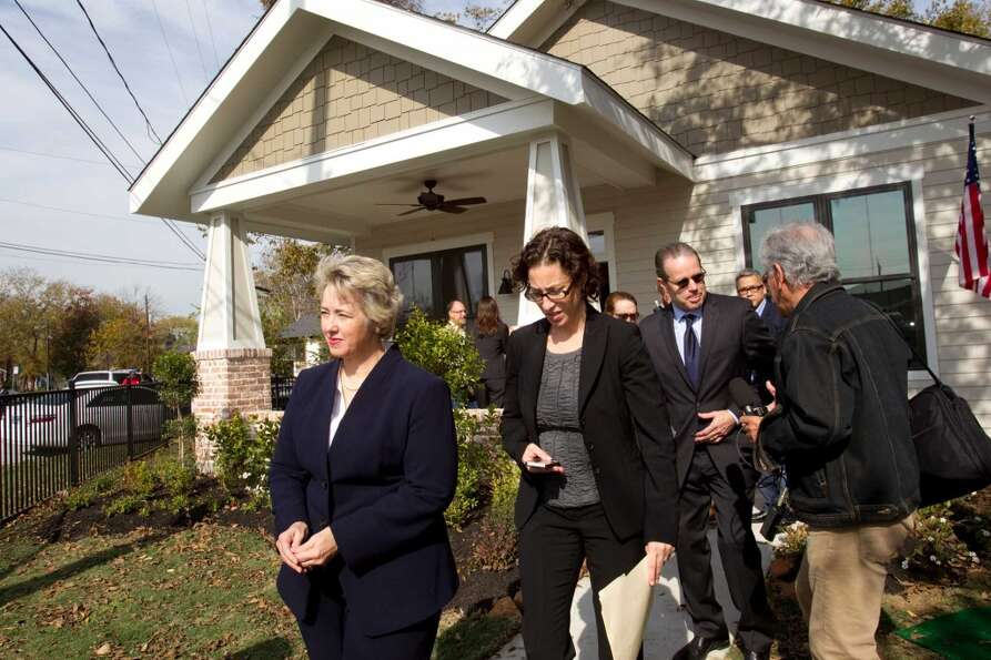 Mayor Annise Parker, left, walks down the sidewalk of a new zero energy home in Independence Heights