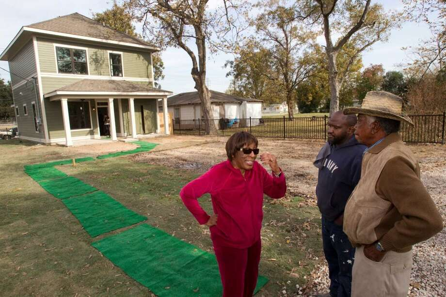 Daisy Snow, left, Kelvin Williams and Cecil Snow, Sr., talk outside one of the two new zero energy homes by HOUZE built in Independence Heights Thursday, Nov. 29, 2012, in Houston. The initial rollout of HOUZE homes, using energy-wise next generation building systems, materials and technologies, was developed through a partnership with the City of Houston. ( Brett Coomer / Houston Chronicle ) (Houston Chronicle)