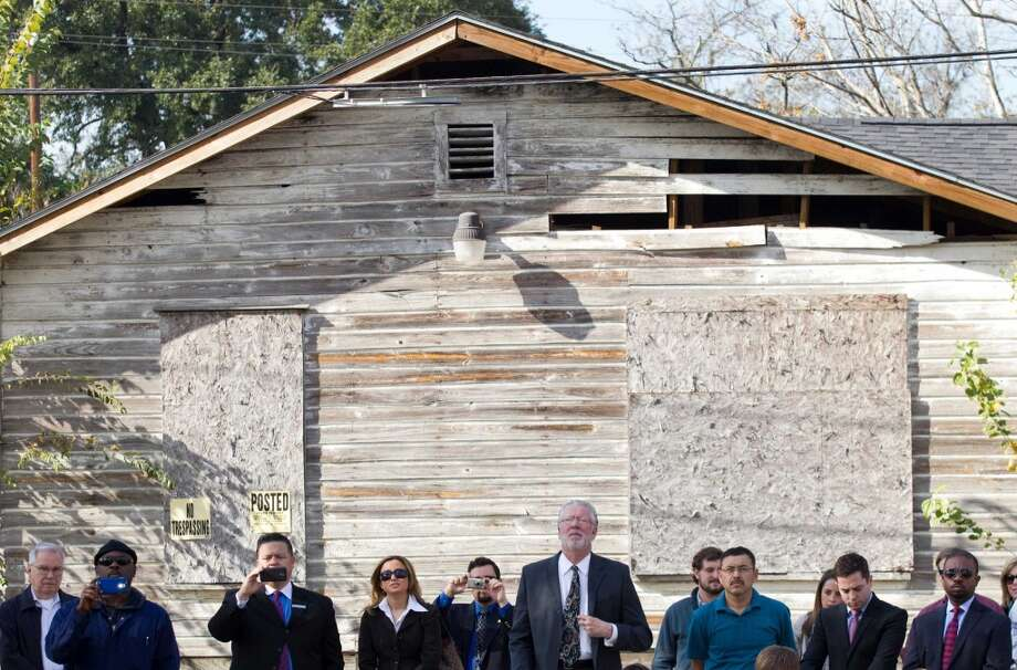 People stand with their backs to an abandoned house as they watch a news conference to unveil of a pair of zero energy homes by HOUZE in Independence Heights Thursday, Nov. 29, 2012, in Houston. The initial rollout of HOUZE homes, using energy-wise next generation building systems, materials and technologies, was developed through a partnership with the City of Houston. ( Brett Coomer / Houston Chronicle ) (Houston Chronicle)
