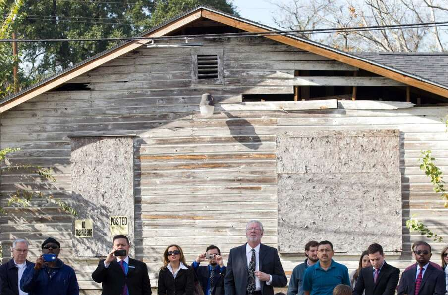 People stand with their backs to an abandoned house as they watch a news conference to unveil of a p