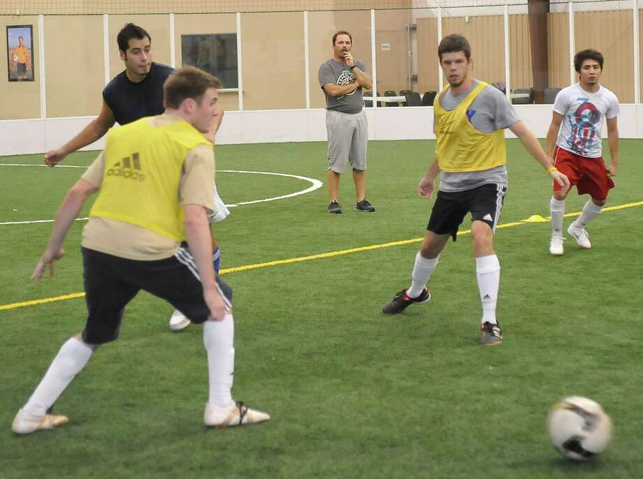 """The Texas Strikers indoor soccer team held a practice at the Quinn Indoor Complex Monday night 11/26/2012. The head coach/general manager is Chris """"Topper"""" Cogan,center, who is watching the players work a drill passing the ball around.  This is the Strikers' first season in the Professional American Soccer League. Cogan also serves as an assistant coach on the Lamar women's soccer team.     Dave Ryan/The Enterprise Photo: Dave Ryan"""
