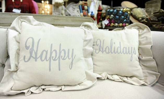 Happy Holidays pillows from Urban Habitat are available for purchase during the Main Street Market on Thursday, November 29, 2012.  The market, presented by the Junior League of Beaumont, opened Thursday night, continues from 10 a.m. to 7 p.m. Friday and Saturday and 11 a.m. to 5 p.m. Sunday at the Beaumont Civic Center. Friday morning at 10 a.m., guests can take part in the Holiday Happy Hour brunch, which includes a style show and entertainment. On Saturday, Jingle and Mingle with a style show, entertainment, children's workshop and story time. Santa will be available from 10 a.m. to 2 p.m. Saturday for photos with kids. On Sunday, go Cruisin' to Christmas with a style show and entertainment. Throughout the four-day event, vendors will offer jewelry, accessories, clothing, shoes, handbags, maternity items, children's clothing, unique toys, home and holiday décor, food items, wine and more. Admission is $5 for adults and free for children 12 and younger. Photo taken: Randy Edwards/The Enterprise Photo: Randy Edwards