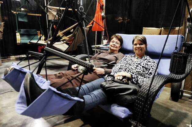Judy Moore and Lisa Bowling relax in swings displayed during the Main Street Market on Thursday, November 29, 2012.  The market, presented by the Junior League of Beaumont, opened Thursday night, continues from 10 a.m. to 7 p.m. Friday and Saturday and 11 a.m. to 5 p.m. Sunday at the Beaumont Civic Center. Friday morning at 10 a.m., guests can take part in the Holiday Happy Hour brunch, which includes a style show and entertainment. On Saturday, Jingle and Mingle with a style show, entertainment, children's workshop and story time. Santa will be available from 10 a.m. to 2 p.m. Saturday for photos with kids. On Sunday, go Cruisin' to Christmas with a style show and entertainment. Throughout the four-day event, vendors will offer jewelry, accessories, clothing, shoes, handbags, maternity items, children's clothing, unique toys, home and holiday décor, food items, wine and more. Admission is $5 for adults and free for children 12 and younger. Photo taken: Randy Edwards/The Enterprise Photo: Randy Edwards