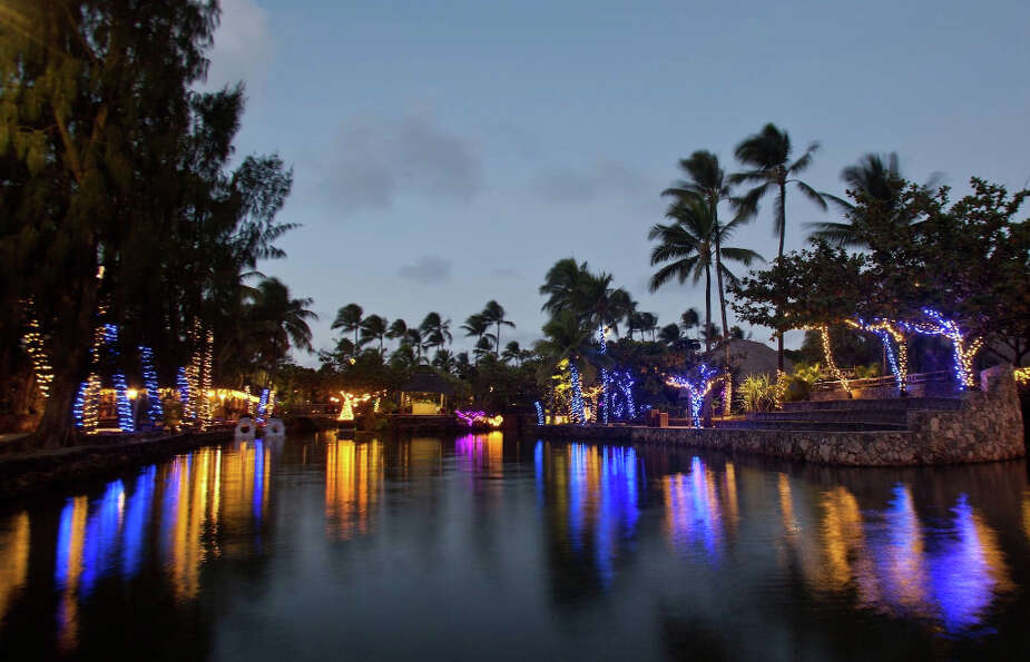 The illuminated riverbanks set the mood for the Christmas in Polynesia canoe ride at the Polynesian