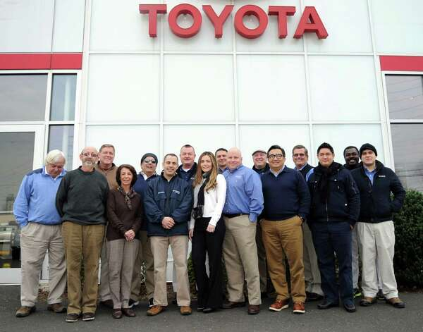Members of Toyota of Stamford's sales and service staff pose for a photo Friday, November 30, 2012, after a Powerball ticket they shared won a $1 million prize. After taxes, each participant will receive about $30,000. Photo: Lindsay Niegelberg / Stamford Advocate