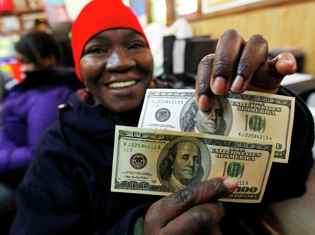 Charlotte Muhammad holds up two $100 dollar bills she got from Secret Santa, at St. Joseph's Social Service Center in Elizabeth, N.J., Thursday, Nov. 29, 2012. The wealthy philanthropist from Kansas City, Mo. known as Secret Santa distributed $100 dollar bills to needy people at St. Joseph's and other locations in Elizabeth.