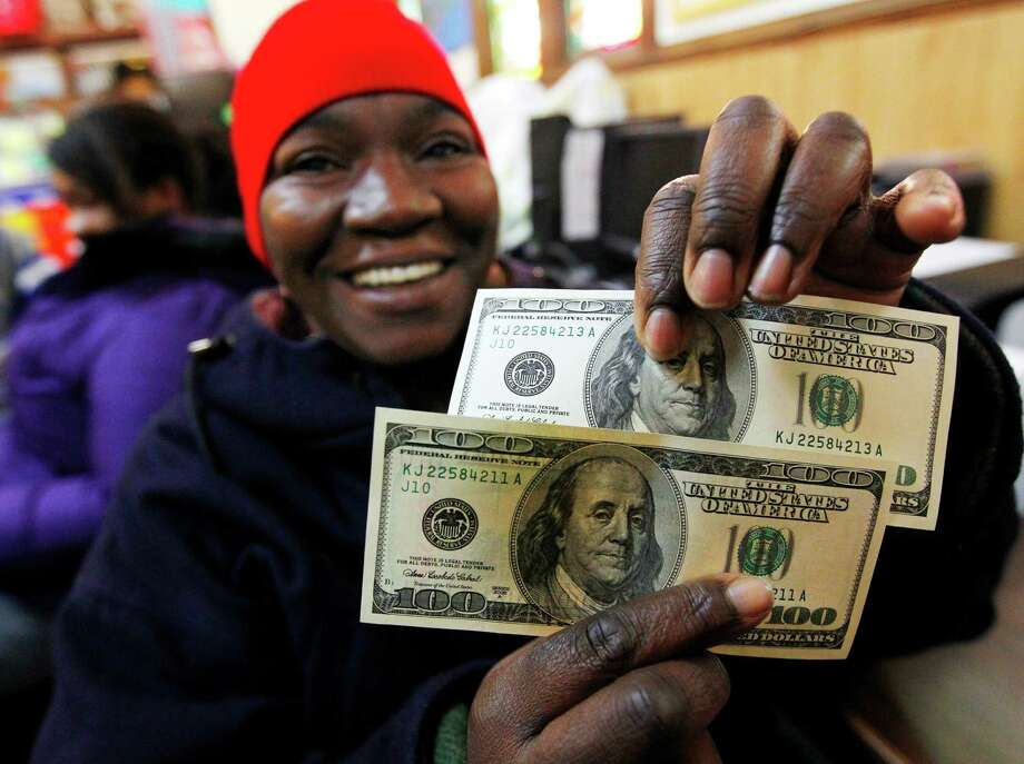 Charlotte Muhammad holds up two $100 dollar bills she got from Secret Santa, at St. Joseph's Social Service Center in Elizabeth, N.J., Thursday, Nov. 29, 2012. The wealthy philanthropist from Kansas City, Mo. known as Secret Santa distributed $100 dollar bills to needy people at St. Joseph's and other locations in Elizabeth. Photo: Rich Schultz, AP / FR27227 AP