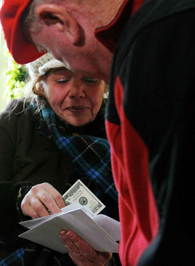 A woman receives a $100 dollar bill from a wealthy philanthropist from Kansas City, Mo.,  known as Secret Santa. Secret Santa distributes $100 dollar bills to needy people at St. Joseph's Social Service Center and other locations in Elizabeth, N.J., Thursday, Nov. 29, 2012. Photo: Rich Schultz, AP / FR27227 AP