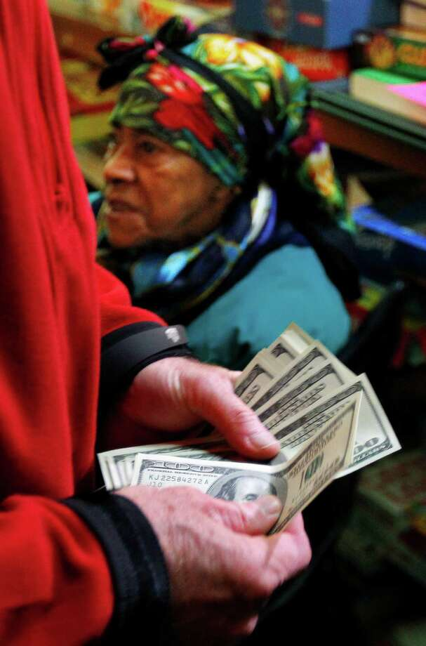 A wealthy philanthropist from Kansas City, Mo., known as Secret Santa, distributes $100 dollar bills to needy people at St. Joseph's Social Service Center in Elizabeth, N.J., Thursday, Nov. 29, 2012. Photo: Rich Schultz, AP / FR27227 AP