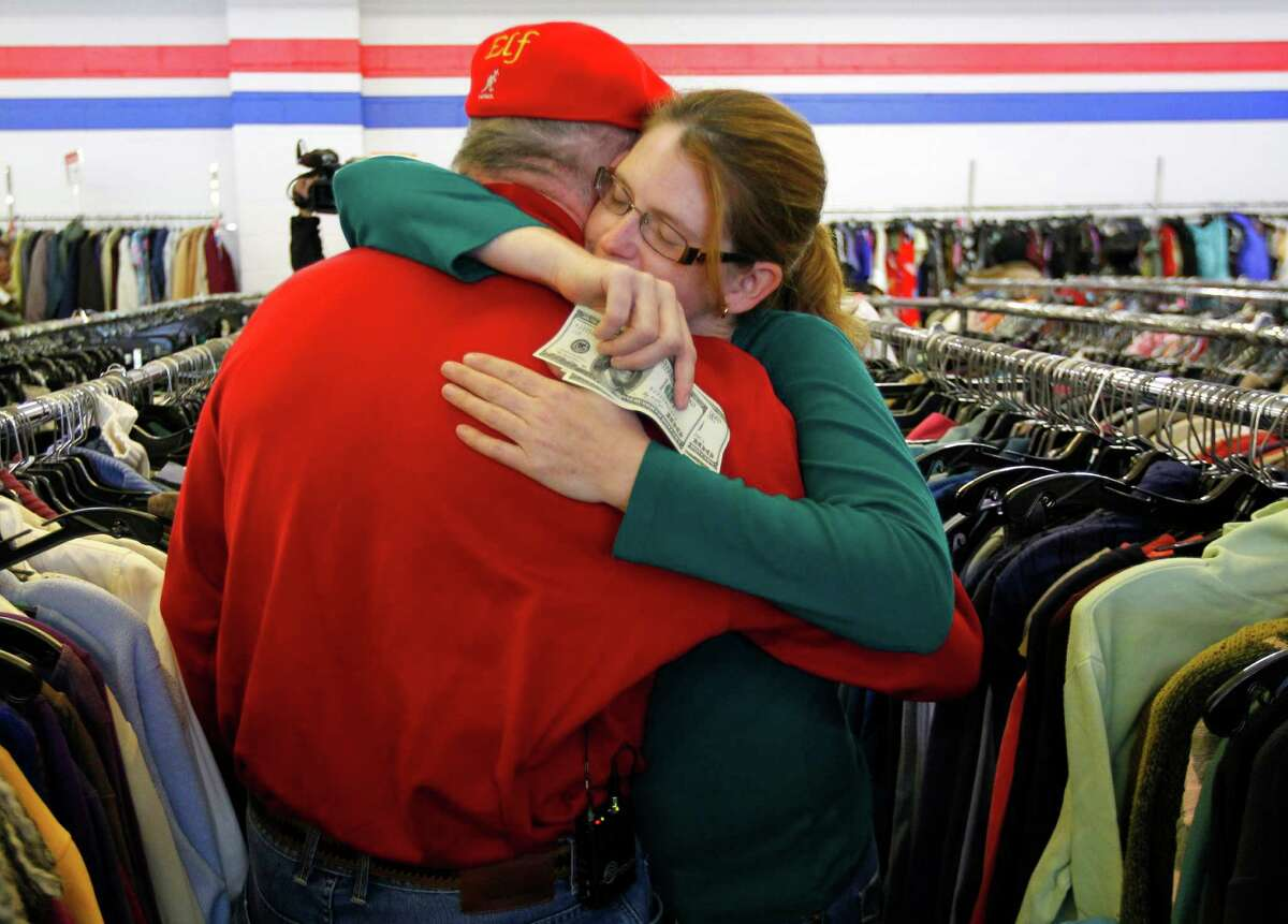 Janice Kennedy hugs Secret Santa after getting a $100 dollar bill from the wealthy philanthropist from Kansas City, Mo. while looking for clothes at the Salvation Army store in the boro of Staten Island, New York, N.Y., Thursday, Nov. 29, 2012. Secret Santa distributed $100 dollar bills to needy people at several locations in Elizabeth, N.J. and Staten Island.