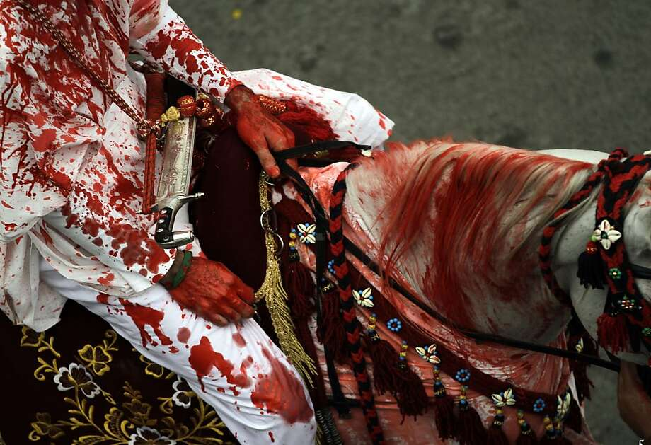 A Bahraini man covered in fake blood rides a horse in Sanabis, Bahrain, during a procession to mark the month of Muharram, when Shiites mourn the killing of Imam Hussein, prophet Muhammad's grandson. Photo: Hasan Jamali, Associated Press