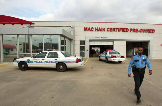 An officer walks back to his car after a shooting occurred at a Mac Haik Pre-Owned dealership Friday, Nov. 30, 2012, in Houston. The alleged shooter was a salesman who shot the sales manager after a confrontation occured police said. Photo: Cody Duty, Houston Chronicle / © 2012 Houston Chronicle