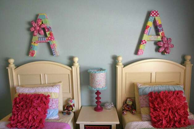 Kristi Hutton redesigned a room for her 3-year-old twins. She used a glue gun and fabric to make letters that hang over the girls' beds. Photo: Helen L. Montoya, San Antonio Express-News / ©SAN ANTONIO EXPRESS-NEWS