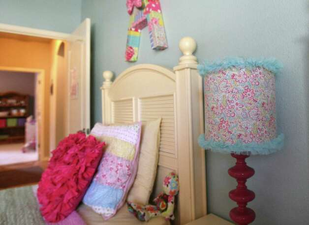 Kristi Hutton recently redesigned the room for her 3-year-old twins, Alex and Avery. Hutton repainted an armoire she bought off craigslist and used a glue gun and fabric to make letters that hang over the girls' beds, among other crafty additions. Photo: Helen L. Montoya, Staff / ©SAN ANTONIO EXPRESS-NEWS