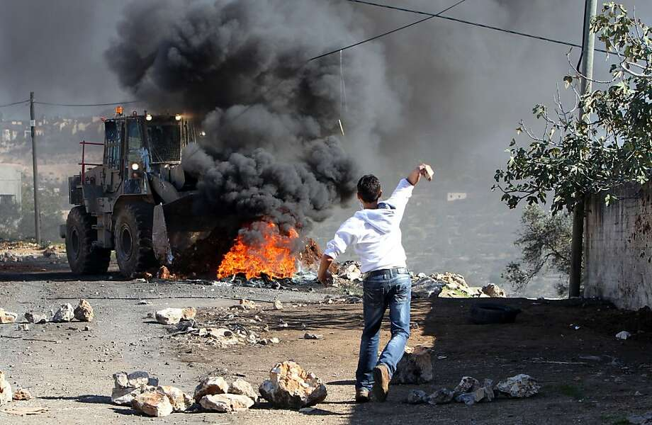 A Palestinian protester throws a stone toward an Israeli bulldozer on the sidelines of a demonstration against the expropriations by Israel in the West Bank village of Kafr Qaddum, near Nablus, on November 30, 2012. Israel is to build 3000 new settler homes in east Jerusalem and the West Bank after the Palestinians won recognition as a non-member state at the United Nations, an Israeli official told AFP on today. Photo: Jaafar Ashtiyeh, AFP/Getty Images