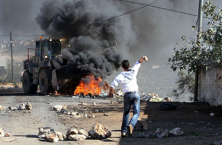 A Palestinian protester throws a stone toward an Israeli bulldozer on the sidelines of a demonstrati