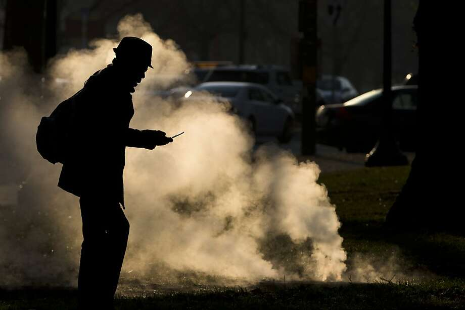 Cold call:A pedestrian uses his phone as steam pours from a grate near the Philadelphia Museum of Art. Photo: Matt Rourke, Associated Press