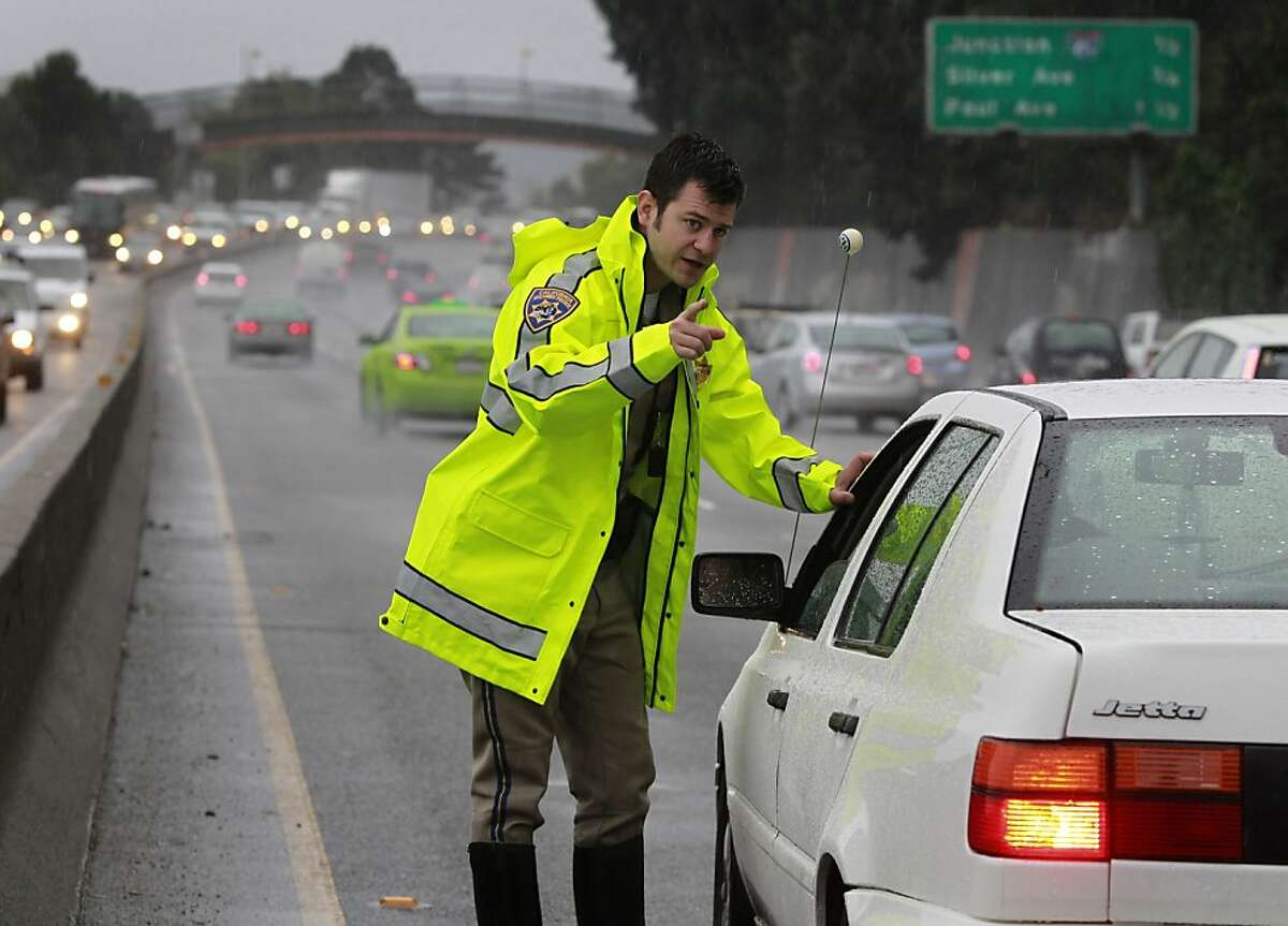 California Highway Patrol officer Mike Ferguson gives instructions to a driver involved in a minor three car accident on southbound Highway 101 near Cesar Chavez Boulevard during Friday's rainstorm in San Francisco, Calif. on Nov. 30, 2012.