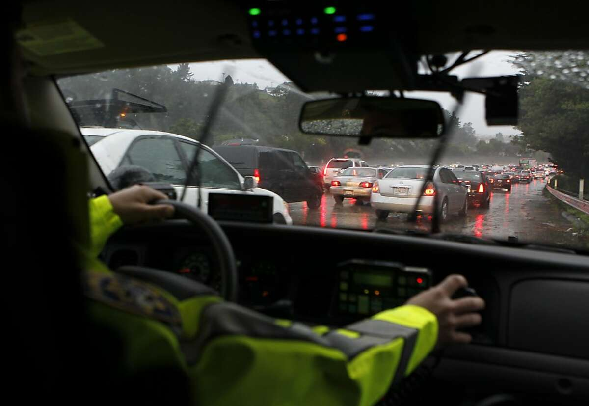 California Highway Patrol officer Mike Ferguson drives on the right shoulder past stopped traffic while responding to a single car accident on northbound Interstate 280 near Avalon Drive during Friday's rainstorm in San Bruno, Calif. on Nov. 30, 2012.