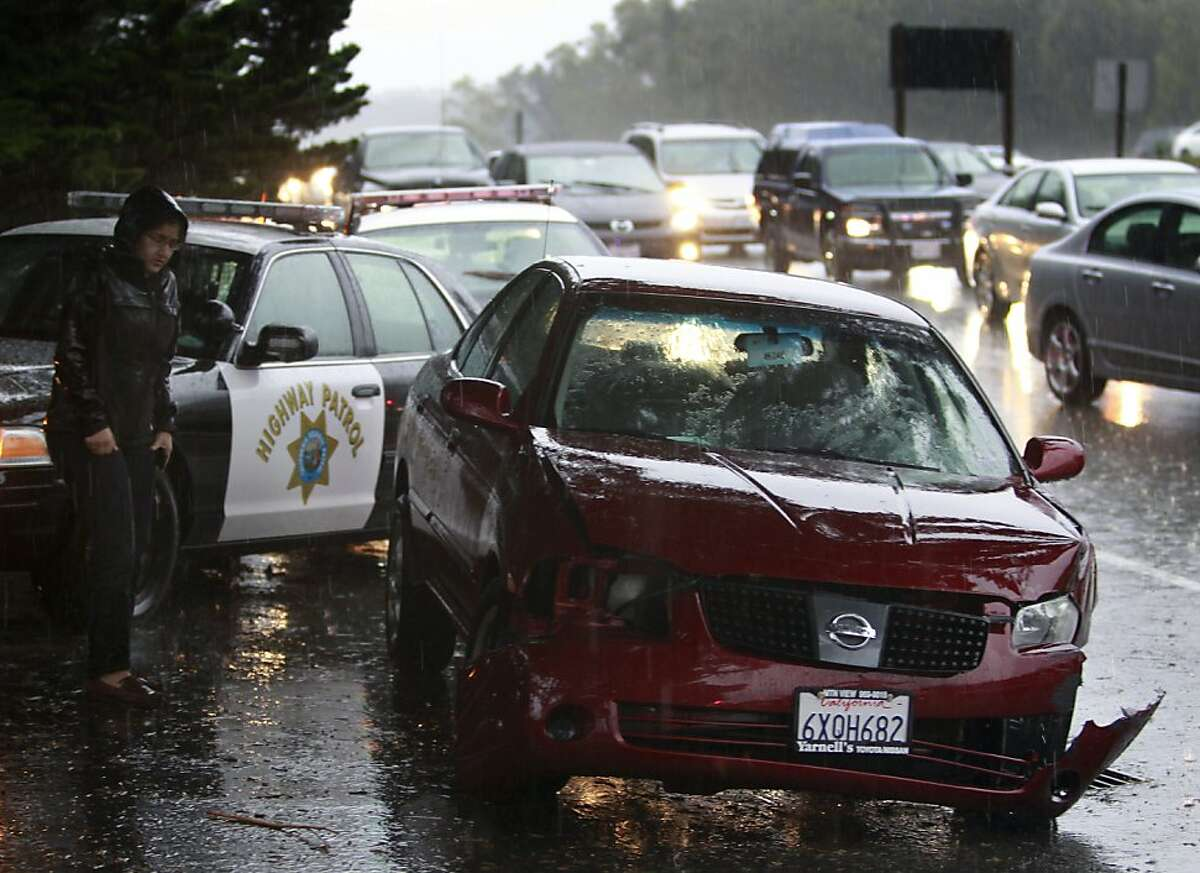 A driver waits to talk to California Highway Patrol officers next to her damaged car after she hit the center divider on northbound Interstate 280 near Avalon Drive during Friday's rainstorm in San Bruno, Calif. on Nov. 30, 2012.