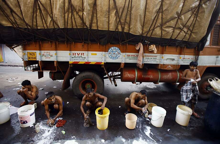 After a day in the fields,Indian migrant workers wash their clothes on a Mumbai roadside. They must pay 10 rupees (18 cents) for a bucket of water for bathing and washing. Photo: Rafiq Maqbool, Associated Press