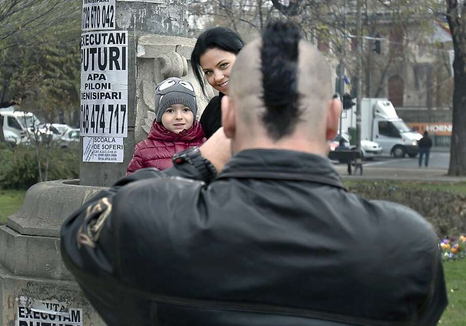 Mohawk memento:A dad takes a picture of the wife and kid in downtown Bucharest. Photo: Vadim Ghirda, Associated Press